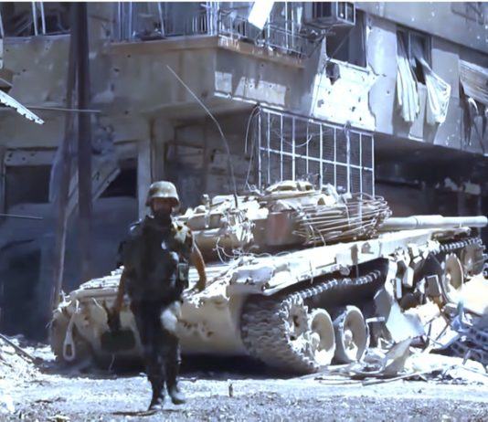 Soldat der Syrischen Armee. Foto News Channel Online. https://www.youtube.com/watch?v=w0-puVP8lGg, CC BY 3.0, Wikimedia Commons.