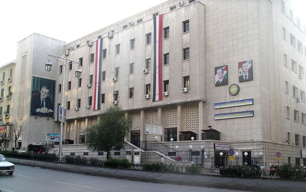 Das Hauptgebäude der Post in Damaskus, mit Bildern von Hafez al-Assad und seinem Sohn Baschar al-Assad. Foto Patrickneil - Eigenes Werk, CC BY-SA 3.0, Wikimedia Commons.