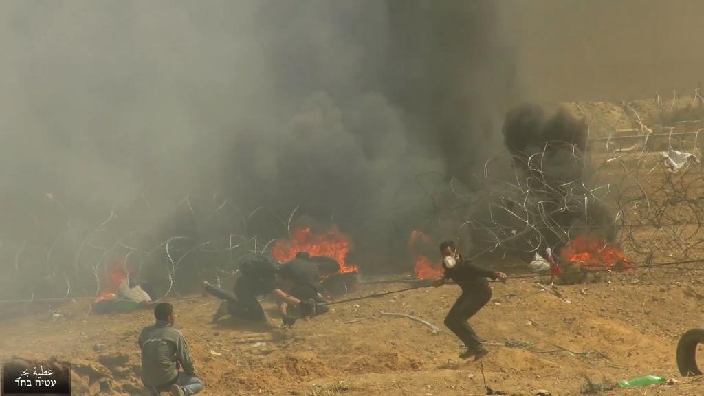 Palästinenser in Gaza versuchen, einen Teil des Grenzzauns mit Israel zu durchbrechen, 30. März 2018. Foto Screenshot Ateya Bahar/Youtube.