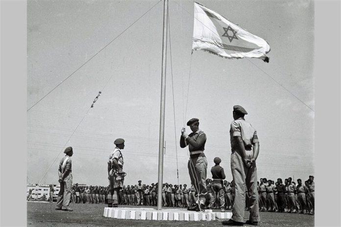 Weniger als 3 Wochen vor Israels Unabhängigkeit wird die Flagge des zukünftigen jüdischen Staates bei einer Morgenparade auf einer Trainingsbasis der jungen israelischen Verteidigungskräfte am 27. April 1948 im noch britischen Mandat für Palästina gehisst. Foto Zoltan Kluger/GPO