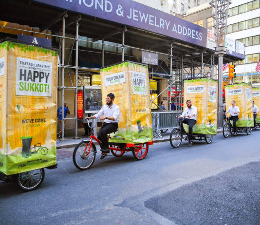 Fahrrad-Sukkah Parade auf der Fifth Avenue in New York City am Montag, 6. Oktober 2014. Foto Itzik Roytman / Chabad.org, https://www.flickr.com/photos/chabadlubavitch/31943946781, Attribution 4.0 International (CC BY 4.0)