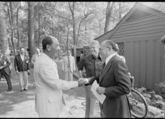 Jimmy Carter beobachtet, wie Anwar Sadat und Menahem Begin sich für eines ihrer Treffen im Camp David begrüssen. Foto U.S. National Archives and Records Administration, Public Domain, https://commons.wikimedia.org/w/index.php?curid=16582502