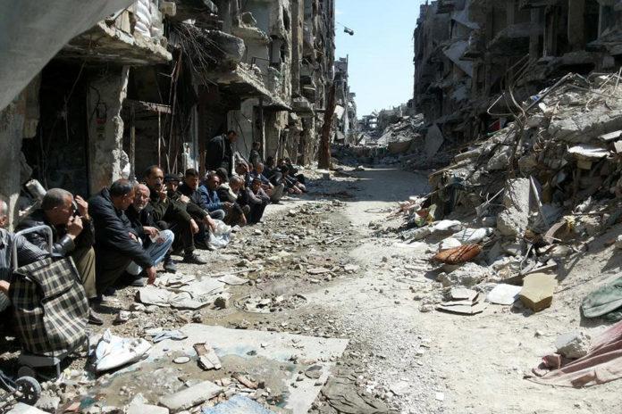 Die 3.903 Palästinenser, die in den letzten sieben Jahren in Syrien getötet wurden, sind für westliche Journalisten und ihre Redakteure nicht von Interesse. Palästinensische Männer sitzen inmitten der Trümmer im Flüchtlingslager Yarmouk, Syrien. Foto UNRWA