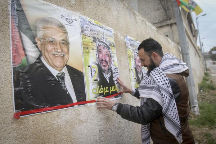 Palästinenser hängen Poster, die den verstorbenen palästinensischen Führer Yasser Arafat und den palästinensischen Präsidenten Mahmoud Abbas in der Stadt Nablus im Westjordanland zeigen. Foto Nasser Ishtayeh/Flash90