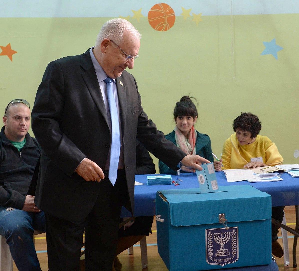 """Der israelische Staatspräsident Reuven """"Ruvi"""" Rivlin an einem blaue Wahlurnen-Pappkarton im Jahr 2015. Foto Mark Neyman / Government Press Office (Israel), CC BY-SA 3.0, https://commons.wikimedia.org/w/index.php?curid=38977948"""