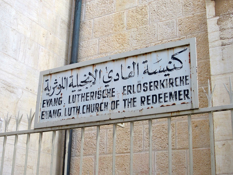 Arabisch, deutsche und englische Beschriftung der Erlöserkirche in Jerusalem. Foto brionv San Francisco, CC BY-SA 2.0, https://commons.wikimedia.org/w/index.php?curid=35075082
