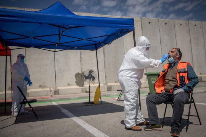 Medizinisches Personal von Magen David Adom bei einer Drive-Through-Stelle zur Entnahme von Proben für Coronavirus-Tests im Shuafat-Flüchtlingslager in Ost-Jerusalem, 16. April 2020. Foto Yonatan Sindel/Flash90