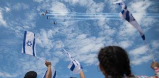 Menschen am Bograschow-Strand in Tel Aviv verfolgen die Militärflugvorführung zum 71. Unabhängigkeitstag Israels am 9. Mai 2019. Foto Hadas Parush/Flash90
