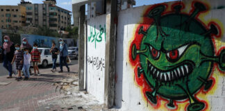 Menschen in Gaza-Stadt gehen an einem Graffiti mit der Darstellung des Coronavirus COVID-19 vorbei. Gaza, 5. Oktober 2020. Foto Majdi Fathi/TPS