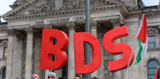"""Anhänger der BDS-Kampagne (Boycott, Divestment and Sanctions) protestieren mit einer Kundgebung vor dem Berliner Reichstagsgebäude gegen den Beschluss des deutschen Bundestags von 17. Mai 2019 mit dem Titel: """"BDS-Bewegung entschlossen entgegentreten - Antisemitismus bekämpfen"""". Foto imago images / snapshot"""