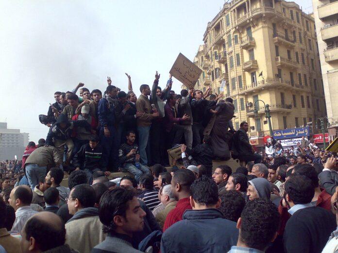 Demonstranten, die am 29. Januar 2011 auf einem Armee-Lastwagen in der Innenstadt von Kairo stehen. Foto Ramy Raoof - Flickr: Demonstrators on Army Truck in Tahrir Square, Cairo, CC BY 2.0, https://commons.wikimedia.org/w/index.php?curid=12851187