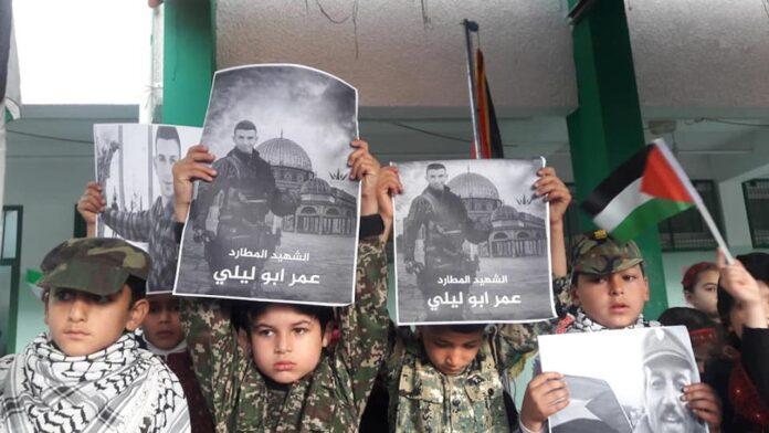 Kinder der Khan Younis Märtyrer Schule halten Plakate mit dem Bild von Omar Abu Layla, der 2019 den israelischen Soldaten Gal Keidan erstochen und Rabbiner Achiad Ettinger erschossen hat. Auf dem Facebook Eintrag der Schule steht: