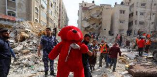 Ein Mann in Gaza trägt einen perfekt sauberen, riesigen roten Stoffteddybär. Laut verschiedenen Medien (z.Bsp. Basler Zeitung 17. Mai 2021) soll der Teddybär aus den Trümmern eines eingestürzten Hauses stammen. Foto IMAGO / ZUMA Wire