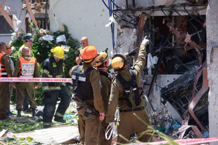 Mitglieder der israelischen Sicherheitskräfte inspizieren ein Wohnhaus, das von einer aus dem Gazastreifen abgefeuerten Rakete getroffen wurde, in der südisraelischen Stadt Ashdod, am 17. Mai 2021. Foto IMAGO / Xinhua