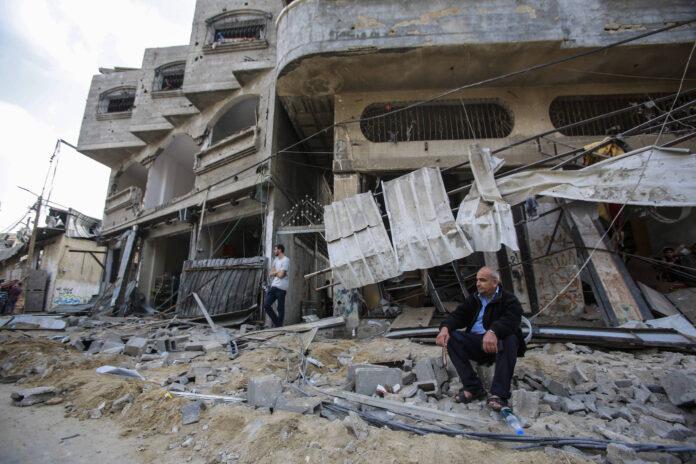 Ein palästinensischer Mann sitzt vor einem zerstörten Haus nach israelischen Luftangriffen in Gaza. Foto IMAGO / ZUMA Wire