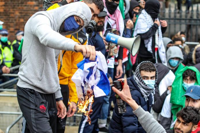 22. Mai 2021: Demonstranten setzen eine israelische Flagge in Brand, als sie sich in der Nähe der israelischen Botschaft in Kensington, im Zentrum Londons versammeln. Unter den teilnehmenden Gruppen waren Sektionen der National Education Gewerkschaft, die Palestine Solidarity Campaign, Palestine Action und Stop The War Coalition. Foto IMAGO / VXPictures.com