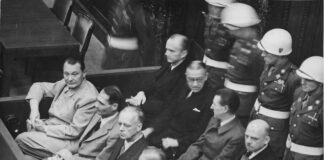 Göring, Hess, von Ribbentrop, Keitel (vordere Reihe von links), Dönitz, Raeder, von Schirach und Sauckel (dahinter). Diese Datei ist im Bestand der National Archives and Records Administration verfügbar, katalogisiert unter dem National Archives Identifier (NAID) 540128., Gemeinfrei, https://commons.wikimedia.org/w/index.php?curid=182386