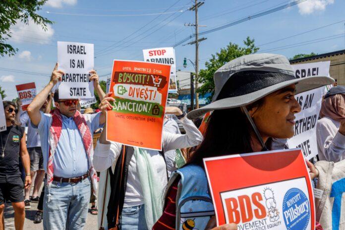 Demonstranten halten Plakate, auf denen sie zum Boykott israelischer Produkte aufrufen. Foto IMAGO / ZUMA Wire
